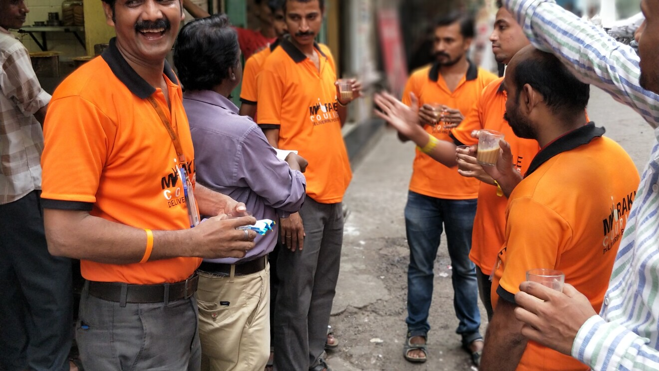 Amazon associates orange shirts communicate with each other in sign language on a street in Mumbai, India.