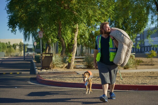 A dog carries a dog bed and leads a dog through a parking lot.