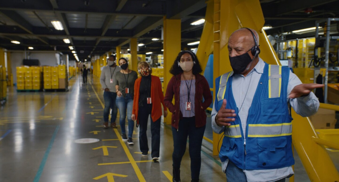 A man wearing a mask leads a line of four masked individuals on a tour at an Amazon fulfillment center.