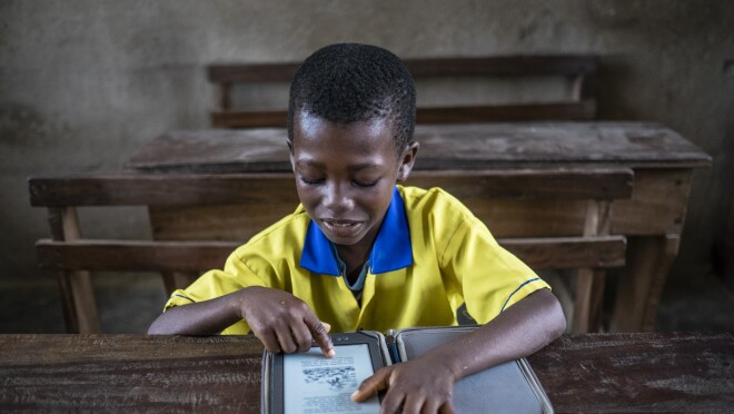 A young boy in a yellow and blue school uniform reads from his Kindle on top of a battered wooden desk.