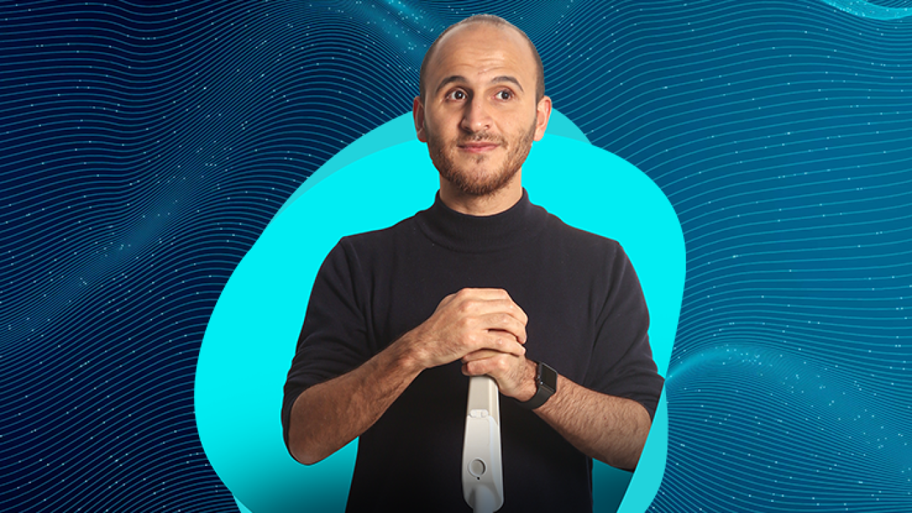 Kürşat Ceylan, co-founder of WeWALK holds a smart handle and wears a black shirt. He stands in front of  a blue graphic.