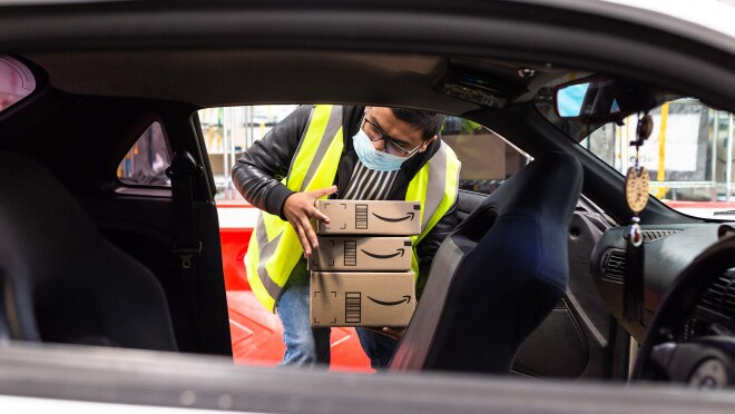 An image of an Amazon delivery driver holding packages while looking into his car. He is wearing a neon safety vest.