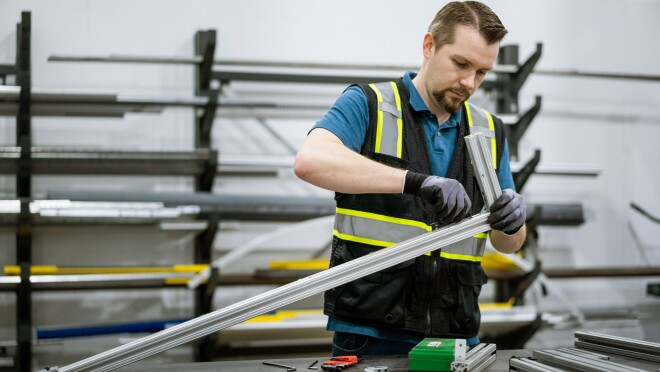 A man in a safety vest assembles a metal device.