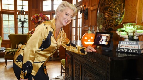 Image of a woman leaning on a table in her home. The table has an Echo Show device on it as well as Halloween decorations.