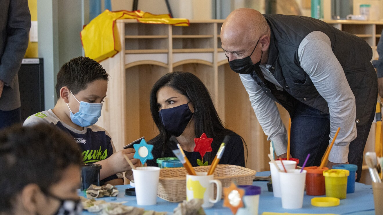 An image of Jeff Bezos and Lauren at an arts and crafts table with children staying at the Mary's Place Family Center.