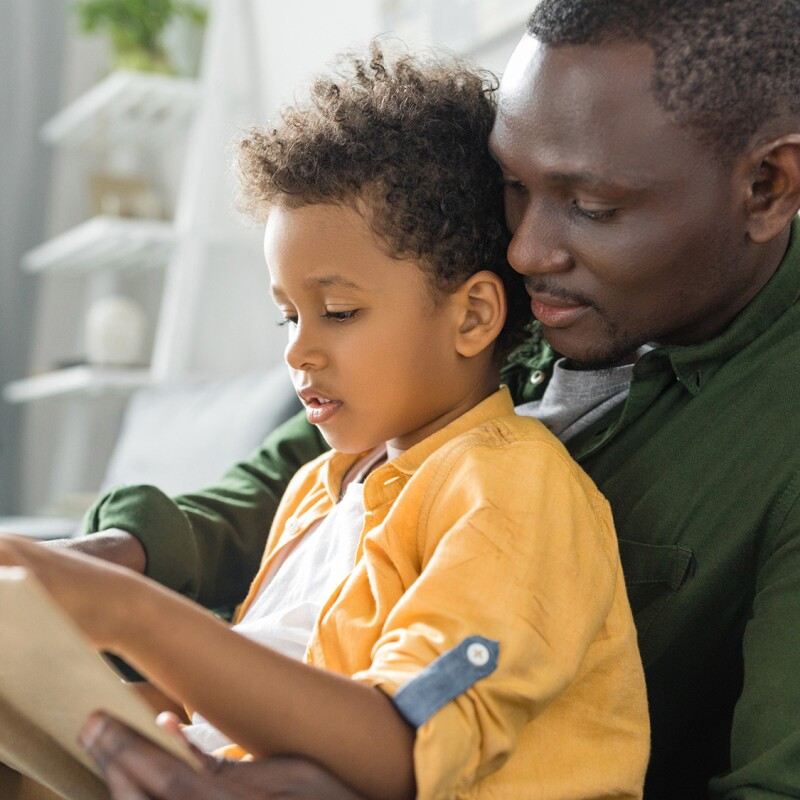 An image of a father and son sitting on a couch together. They are holding a book and the child is reading to his father.
