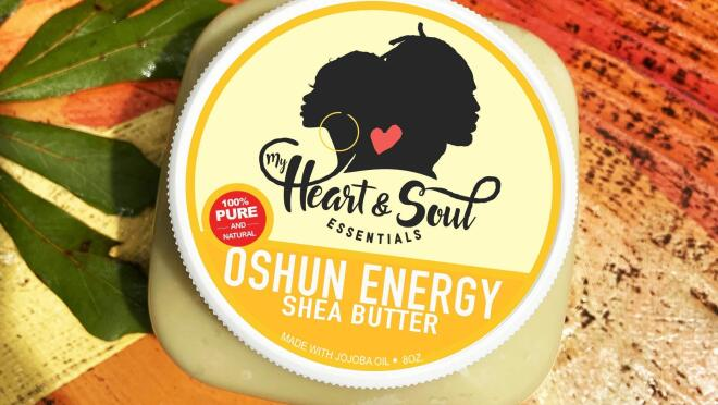 A top-down view of a shea butter product from My Heart and Soul Essentials sits on a wooden table.