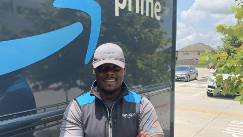 """An image of a man standing in front of an Amazon delivery truck with the Amazon logo and the words """"Prime"""" written on the side. He is wearing an Amazon-branded hat and vest and smiling with his arms folded in front of him."""