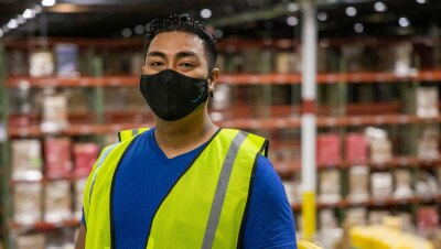 A male Amazon employee wearing a face mask and safety vest looks at the camera as he stands on a platform above the floor of a fulfillment center.