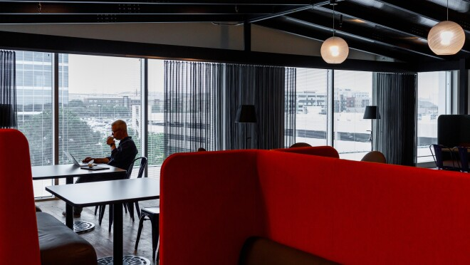 Inside the Amazon office in Austin, Texas, an Amazonian sits at a table near the window, next to him is an empty table. In the foreground are high-back red booths.