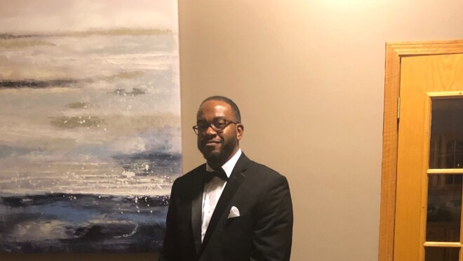 A man in a tuxedo stands in a living room.
