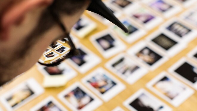 In the upper-left corner of the image, a man in eyeglasses is photographed from behind. None of his body and only part of his head is visible. He looks down at rows of photographic prints on a desk. The only part of the image in sharp focus is the right lens of the man's glasses, through which it is possible to see some of the photos more clearly.