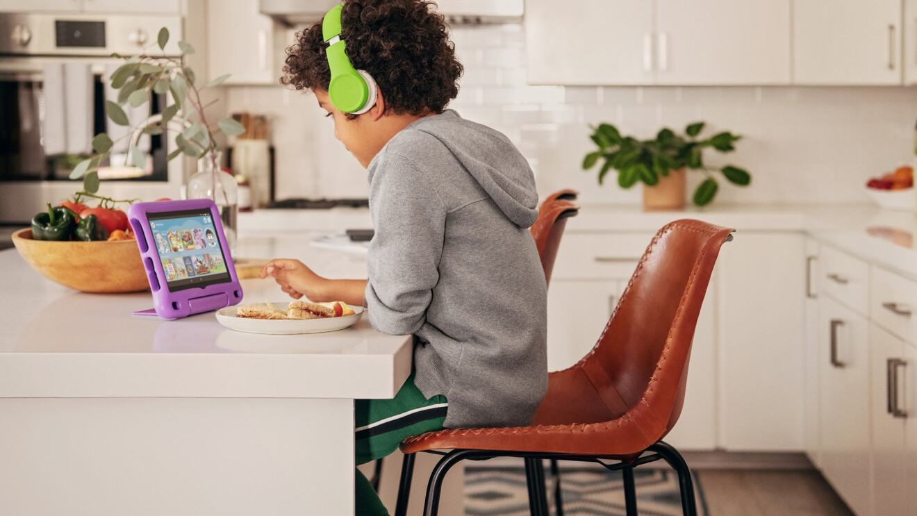 A child sits at a kitchen island, looking at a fire tablet. He wears headphones as he uses the device.