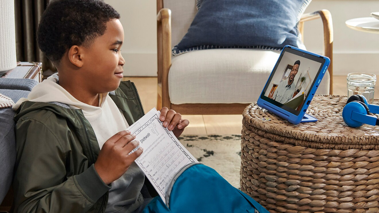 A boy engages with a man on a fire tablet, while pulling homework from a backpack.