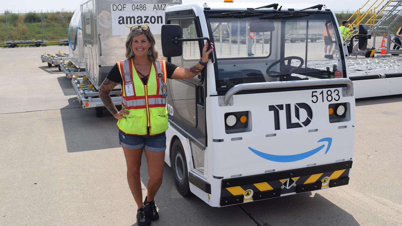 An image of a woman standing in front of a truck that is pulling large metal containers behind it. She is smiling for the photo and wearing a safety vest while working at the Amazon Air Hub in Kentucky.