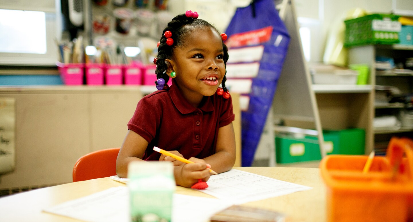 A young girl in a school setting sits with a pen and paper. Blurred out in front of her is a milk carton and snack.