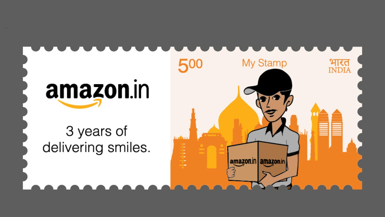 "Image of a stamp worth 5 Indian Rupees. The design shows a delivery person holding a box marked ""amazon.in"" and standing in front of a skyline in the distance. The stamp also bears the words ""amazon.in"" and ""3 years of delivering smiles."""