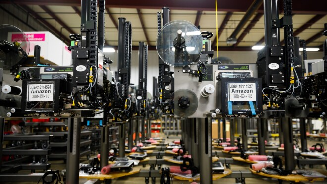 """Rows of metal machines. They have labels on them that say """"Amazon."""" A series of spools of different sizes are on the machines."""