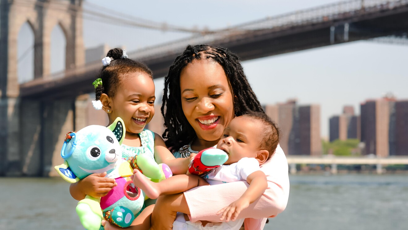 A woman holds a baby and a young child in her arms.  The group is standing in front of a river and a bridge