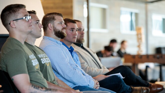 Four men seated together, looking in the same direction. Two men are wearing Warriors@Amazon shirts.