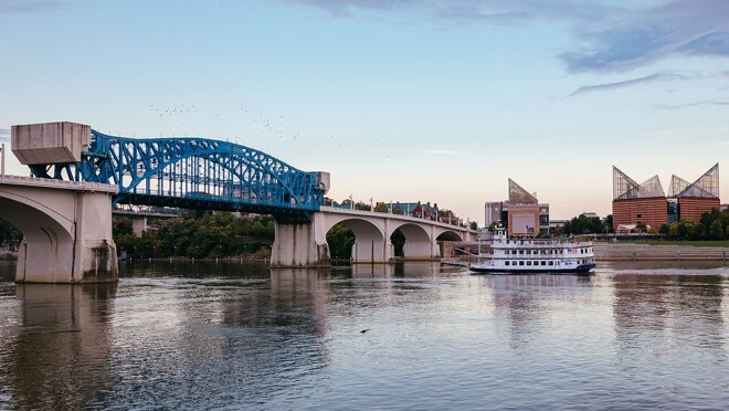 A sweeping view of a river, with a bridge stretched across the width of the body of water. A riverboat is seen in the background, in front of architecturally interesting buildings.