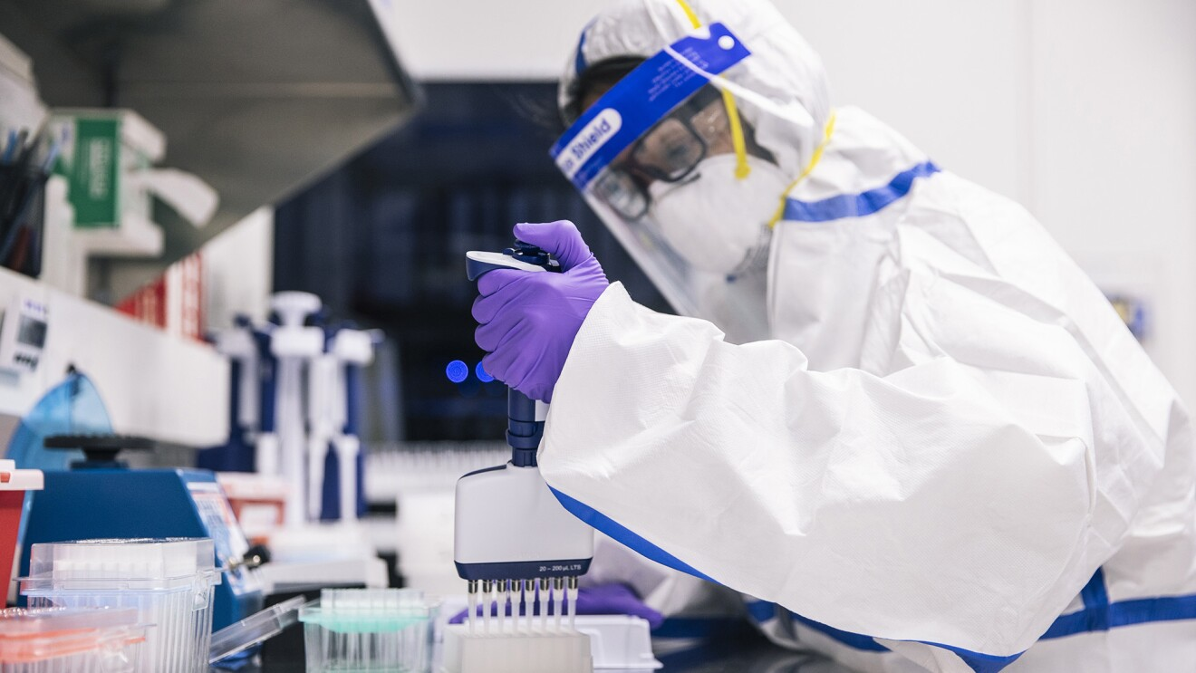 Person in full PPE doing testing in a laboratory setting