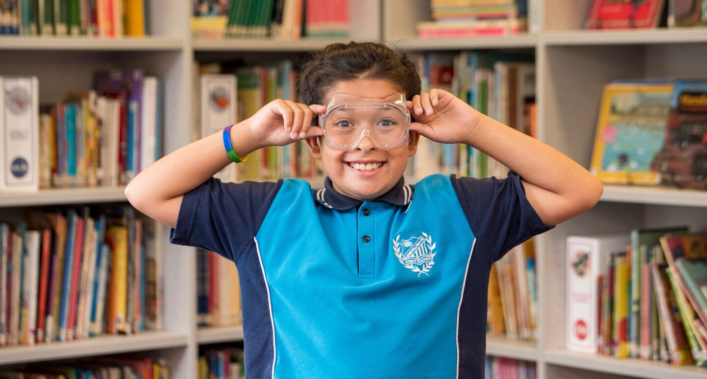 A young boy from Campbellfield Public School in Australia holds protective goggles to his face and gives the camera a goofy grin.