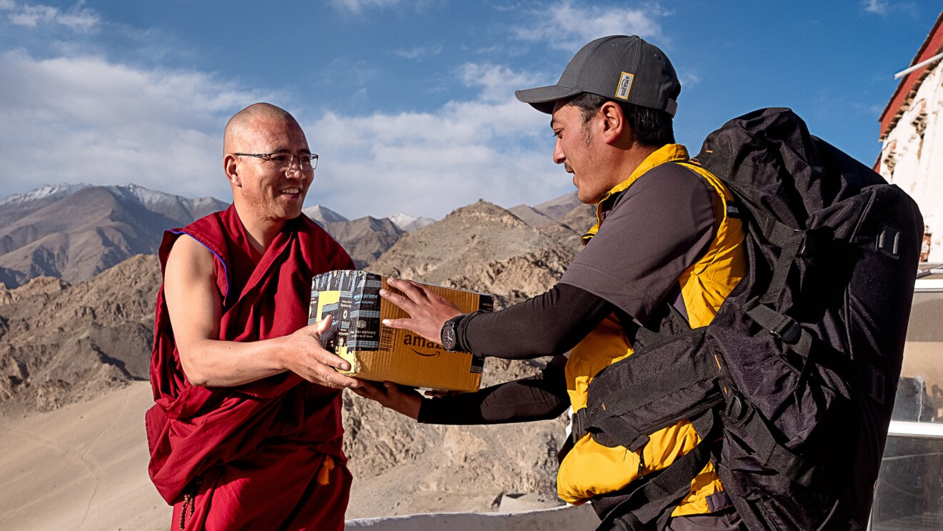 A delivery driver hands an Amazon package to a monk. Behind them, mountains and blue skies are visible.