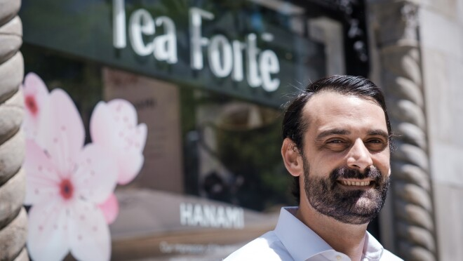 """A man stands in front of a storefront bearing a sign that says """"Tea FortŽé."""""""
