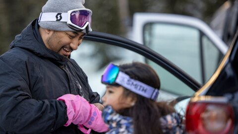 A father smiles as he looks down and helps his young daughter get her winter glove on.