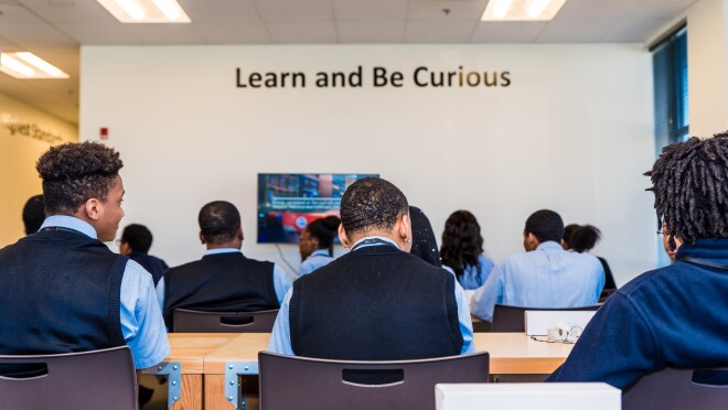 Shown from behind, students are seated at door desks in a classroom space within an Amazon fulfillment center in Etna, Ohio.