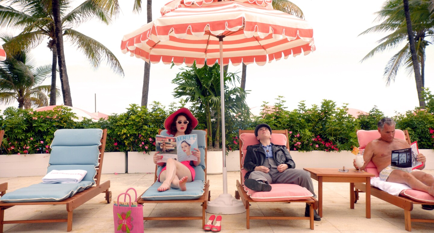 Mrs. Maisel reclines on a lounge chair, poolside, under an umbrella and reading a copy of Vogue. She's joined by Susie Myerson and a man drinking a tropical drink.