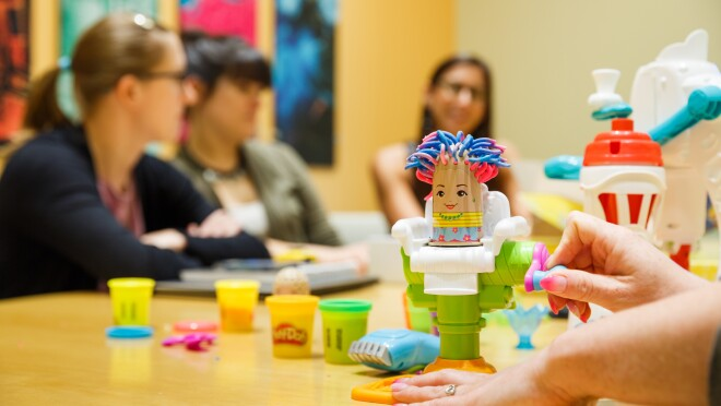 In the foreground, a person turns a crank to demonstrate a Play-Doh toy. In the background, three women sit at a conference table.
