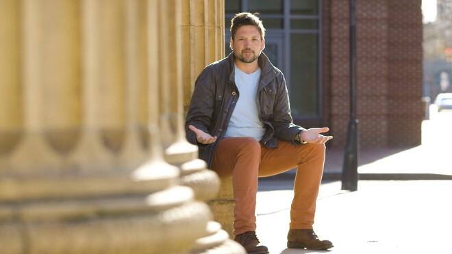 AWS Startup Evangelist Mackenzie Kosut sitting against a wall