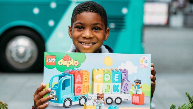 An image of a young boy smiling and holding a building blocks set.