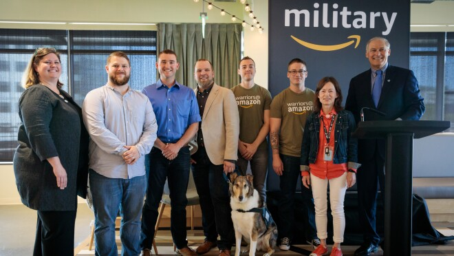 A group of veterans and Amazonians at the Amazon Veteran Technical Apprenticeship (AVTA) program graduation. Two woman and six men stand together, with a dog in the center.