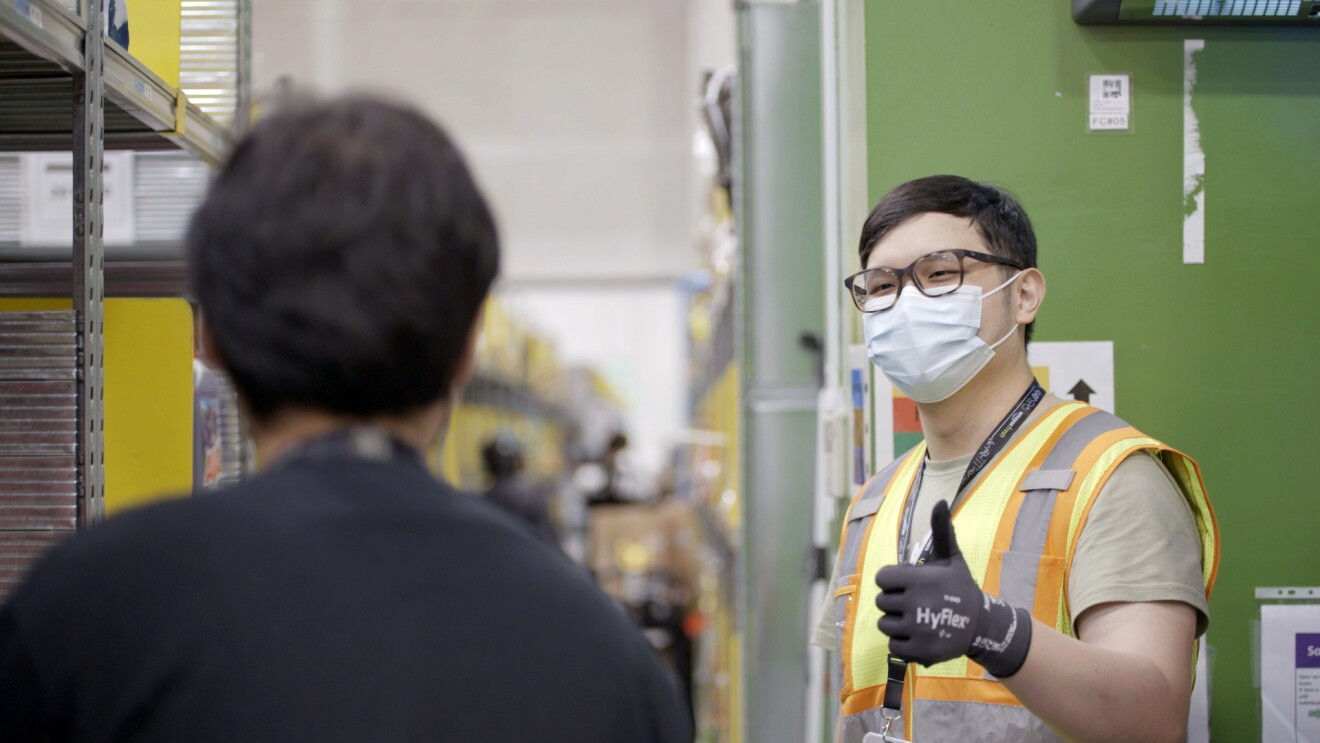 Amazon associate Bryan Chua is seen giving a thumbs up to his colleague at Amazon's Fulfillment Center in Singapore