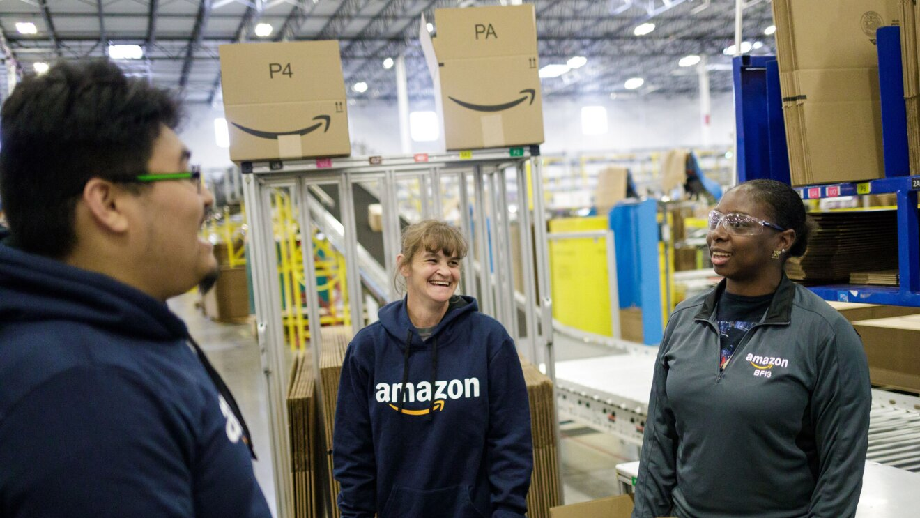 Three Amazon associates share a laugh at work. Behind them is a conveyor with packages on it.