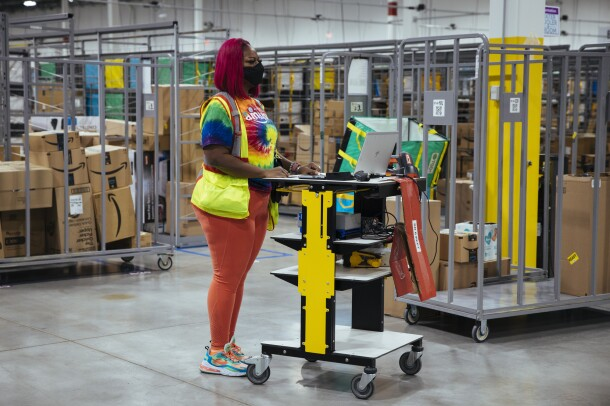 Auhzha Wright stands at her computer workstation in front of boxes and rolling carts inside Amazon's Fulfillment Center