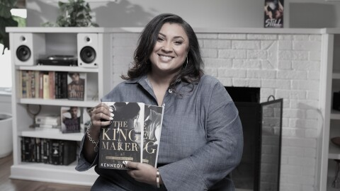 A woman sits in a living room setting, holding two books she wrote and self-published.
