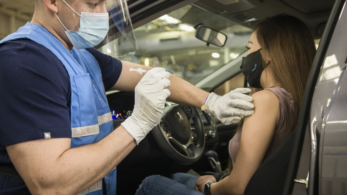 A woman wearing an Amazon mask gets a COVID-19 vaccination while in her vehicle. The man issuing the vaccine is wearing an Amazon vest, mask, face shield, and gloves.