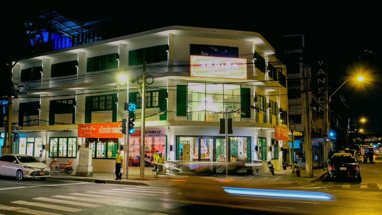 An image of a building with shops on the corner of a street in a city in Thailand.