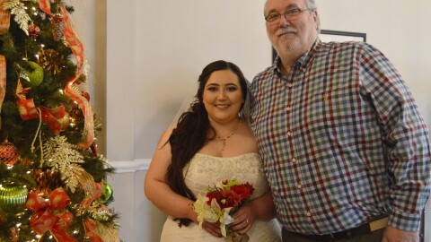 An image of a man and his adult daughter standing for a photo at her wedding. There is a Christmas tree beside them and the daughter is wearing a wedding dress and veil while holding a small bouquet of roses.