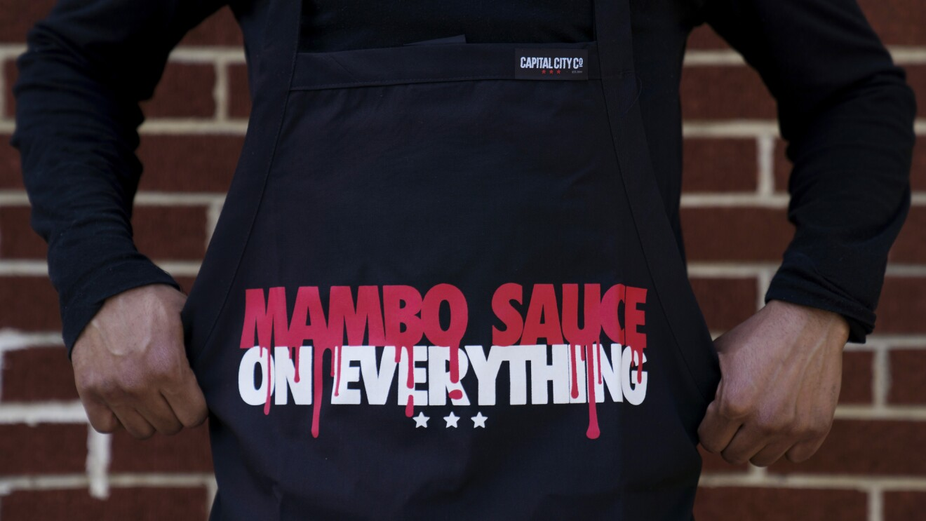"""A person wearing a black apron that reads, """"Mambo Sauce on everything."""""""