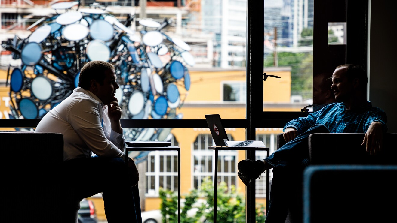 Two Amazon employees sit across from each other and talk in front of a large window that looks out on downtown Seattle.
