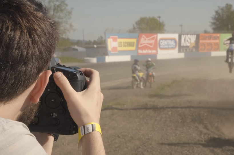 A man trains his camera lens on dirt bike racers as they zoom around the track.