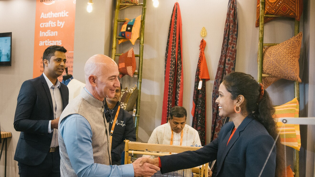 Jeff Bezos shakes the hand of a woman artisan and small business owner.