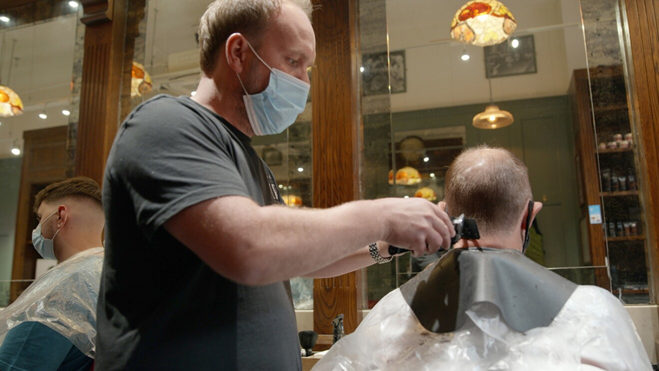 An image of a man wearing a mask while cutting another man's hair.