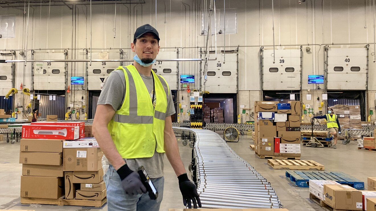 A man wearing a safety vest and a protective mask stands next to a stack of boxes holding a barcode scanner.