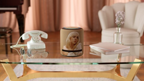 A Billie Eilish Limited-Edition Echo Studio sits on a coffee table next to a vintage telephone, sunglasses, books and flowers in a vase.